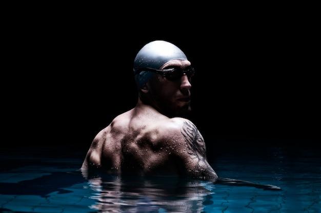 Portret van een zwemmer op een zwarte muur.