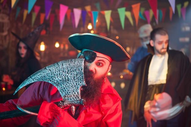Portret van eenogige piraat met bijl die halloween viert. man verkleed als piraat.