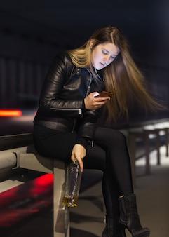 Portret van eenzame vrouw die op de snelweg zit met whisky en mobiele telefoon gebruikt