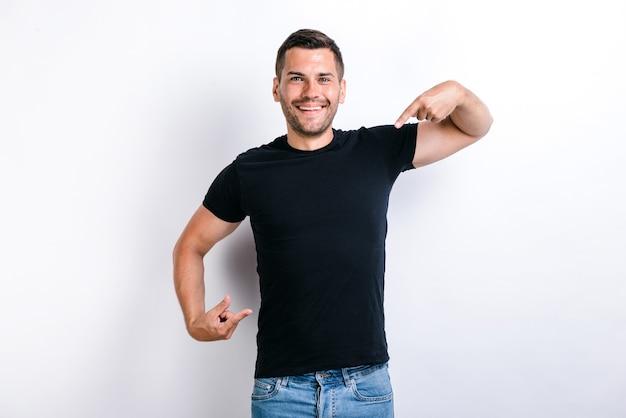 Portret van egoïstische arrogante egoïstische man met baard die naar zichzelf wijst, opschept over succesvolle prestaties, zich trots en hooghartig voelt. indoor studio opname, witte achtergrond