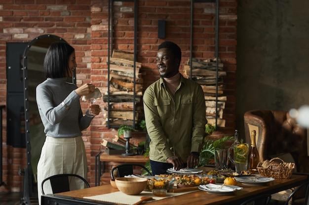Portret van eigentijds gemengd ras paar dat eettafel serveert voor thanksgiving-feest thuis,