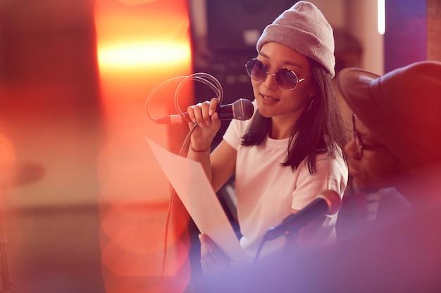 Portret van eigentijdse aziatische vrouw die aan microfoon zingt en songtekstblad houdt