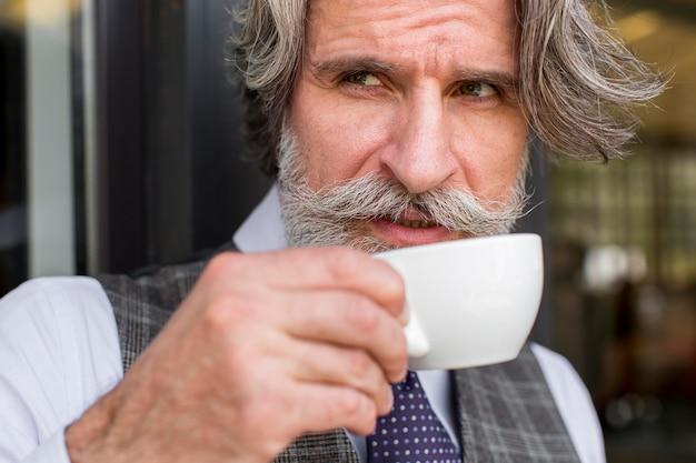 Portret van elegant mannetje dat van koffiekop geniet