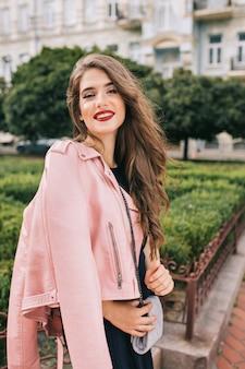 Portret van elegant meisje met lang krullend haar poseren. ze draagt een zwarte jurk, roze jasje, handtas, rode lippen. zij lacht .
