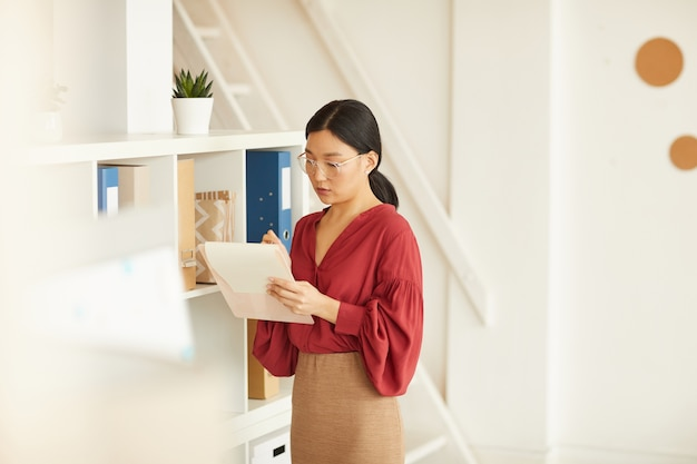 Portret van elegante aziatische zakenvrouw schrijven op klembord terwijl staande door boekenkasten in kantoor, kopieer ruimte