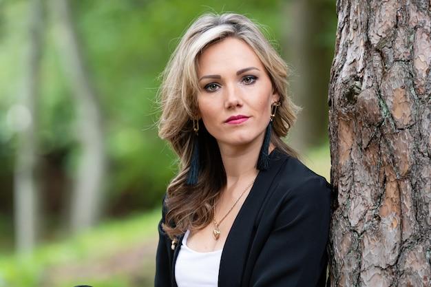 Portret van elegante jonge blonde vrouw op een boomstam in het bos