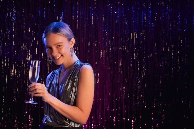 Portret van elegante jonge vrouw met champagneglazen en glimlachend in de camera terwijl poseren tegen sprankelende achtergrond op feestje, kopieer ruimte