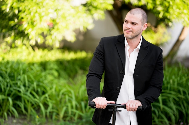Portret van elegante mannelijke paardrijden scooter