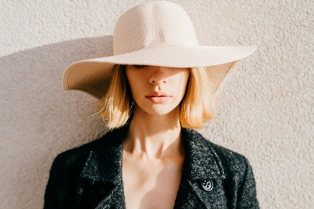 Portret van elegante stijlvolle blonde kort haar meisje in hoed en jasje poseren over beige