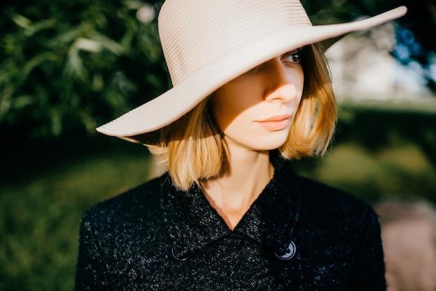 Portret van elegante stijlvolle blonde kort haar meisje in hoed poseren in het park over groene takken