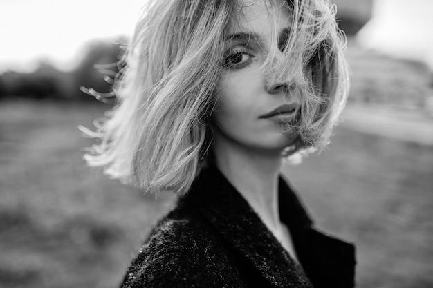 Portret van elegante stijlvolle blonde kort haar meisje met streaming haar poseren in het veld