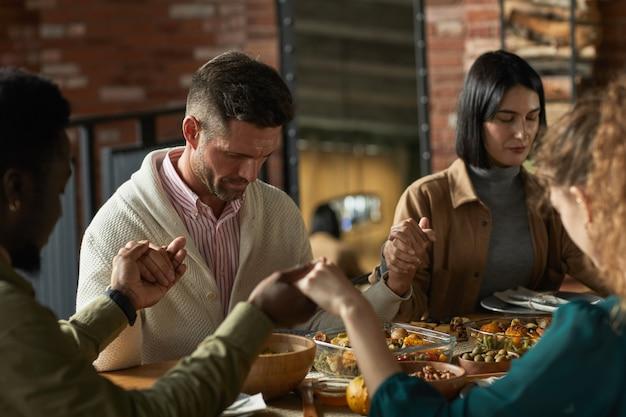 Portret van elegante volwassen man bidden en hand in hand zittend aan tafel tijdens thanksgiving-viering met vrienden en familie,