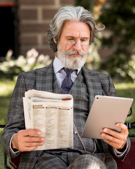 Portret van elegante volwassen man met tablet en krant