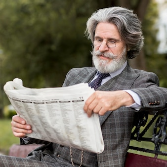Portret van elegante volwassen mannelijke lezing krant