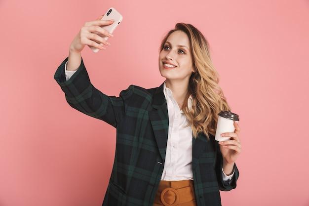 Portret van elegante vrouw 30s in trendy jas met behulp van mobiele telefoon en het drinken van afhaalmaaltijden koffie geïsoleerd op roze