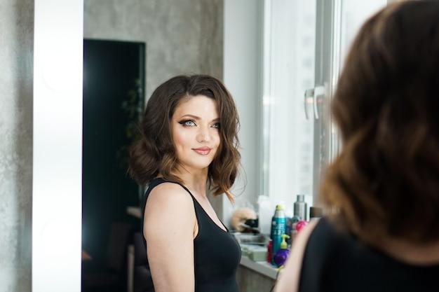 Portret van elegante vrouw met krullend haar reflectie in spiegel kijken