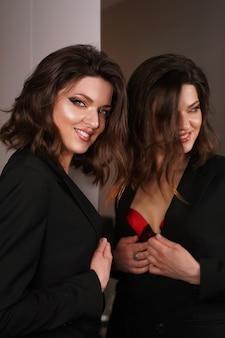 Portret van elegante vrouw met krullend haarbezinning in spiegel