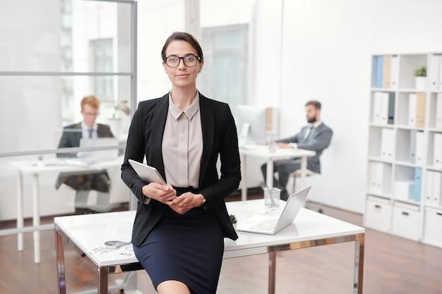 Portret van elegante zakenvrouw bril poseren in kantoor leunend op bureau, kopieer ruimte