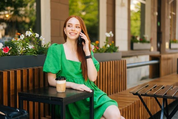 Portret van elegantie mooie jonge vrouw praten via mobiele telefoon zittend aan tafel met koffiekopje op terras in de zomerdag, wegkijkend, onscherpe achtergrond, selectieve aandacht.