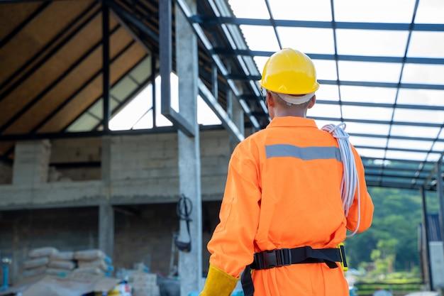 Portret van elektricienarbeider die met elektrische kabel voor installatie in het nieuwe huis voorbereidingen treffen