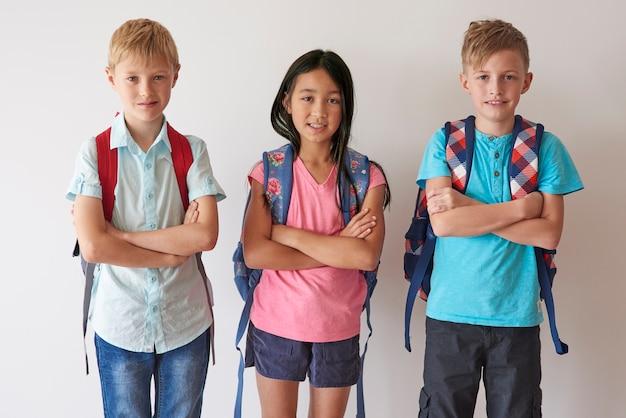 Portret van elementaire kinderen tegen witte muur
