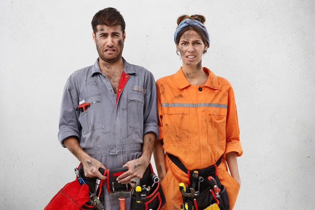 Portret van ellendige uitgeputte servicemedewerkers, die de hele dag iets repareren, vuile gezichten hebben