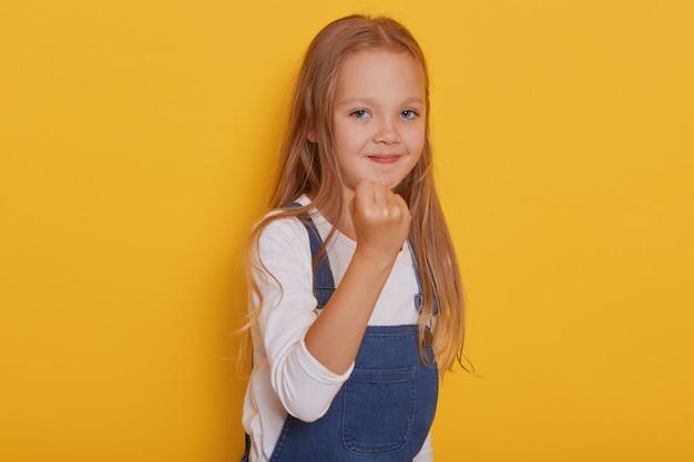 Portret van emotioneel meisje dat over gele achtergrond wordt geïsoleerd, leuk blond kind dat haar vuist toont