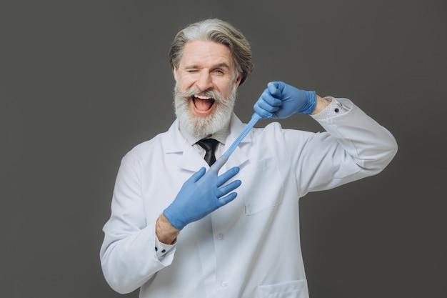 Portret van emotionele arts op grijze muur. grijsharige senor arts gekleed in witte jas en blauwe handschoenen geïsoleerd op een grijze achtergrond.