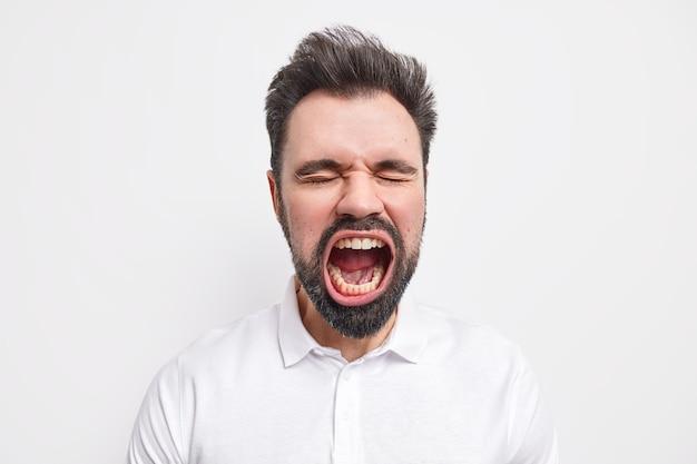 Portret van emotionele, bebaarde gekke europese man houdt mond wijd open, sluit ogen heeft dikke baard gekleed in shirt thick