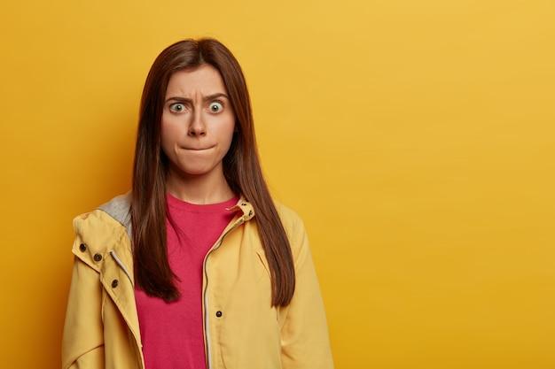 Portret van emotionele bezorgd europese vrouw drukt op de lippen, probeert haar emoties te beheersen, wenkbrauwen optrekken, draagt roze trui en anorak