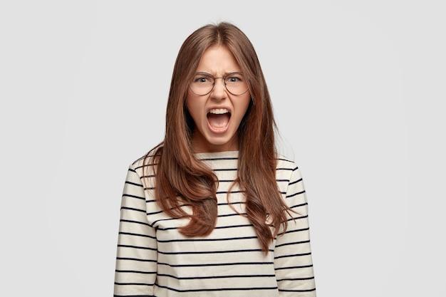 Portret van emotionele brunette vrouw schreeuwt heel hard, heeft een uitdrukking van ontevredenheid, fronst gezicht van ongenoegen