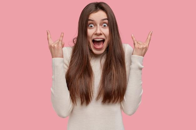 Portret van emotionele donkerharige jonge vrouw maakt rock n roll-gebaar, luistert naar heavy metal, roept luid uit