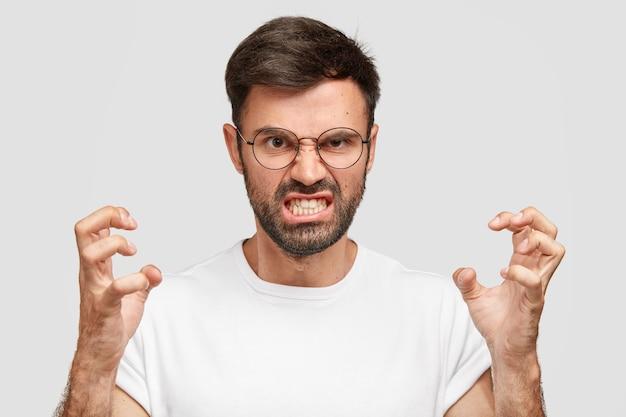 Portret van emotionele geïrriteerde geïrriteerde ongeschoren man klemt tanden en gebaren boos terwijl ruzie met vrouw