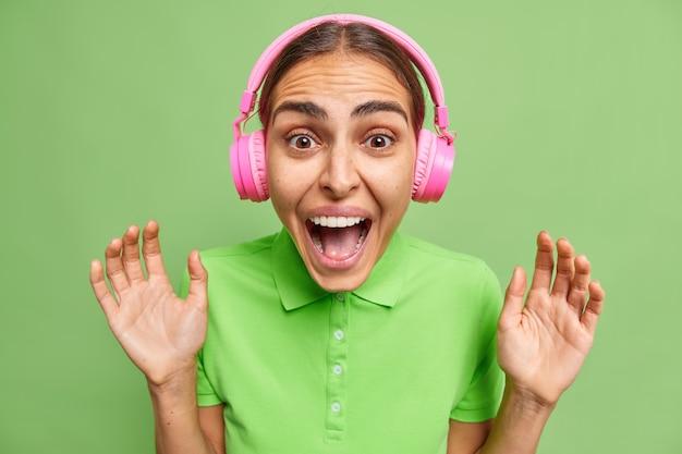 Portret van emotionele jonge vrouw roept luid houdt handpalmen omhoog en mond wijd geopend reageert op iets geweldigs gekleed in casual t-shirt geïsoleerd over groene muur