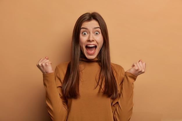 Portret van emotionele juichende vrouw met europese uitstraling, balde vuisten, ontdekt over haar overwinning, balde vuisten met triomf, deelt succes