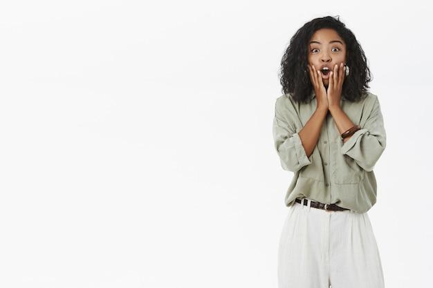Portret van emotionele onder de indruk donkere vrouwelijke werknemer die reageert op verrassend nieuws
