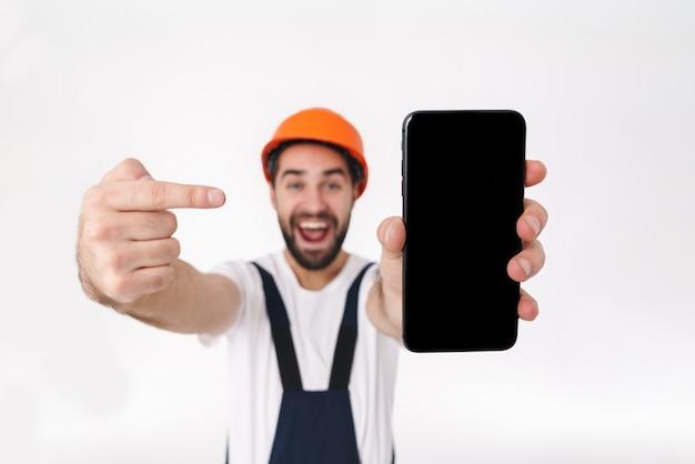 Portret van emotionele positieve jongeman bouwer in helm geïsoleerd over witte muur met weergave van wijzende mobiele telefoon.