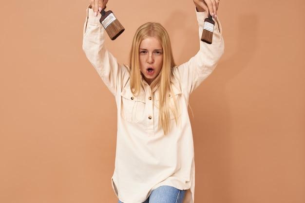 Portret van emotionele vrolijke jonge vrouw met plezier binnenshuis tijdens het schilderen van muren in haar appartement, met twee verfborstels, grappige grimas maken, mond wijd openen