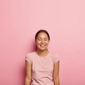 Portret van emotiove tevreden aziatische vrouw met natuurlijke schoonheid, donker gekamd haar, lacht vrolijk, houdt de ogen gesloten, draagt casual t-shirt, geïsoleerd op roze muur. mensen, etniciteit, positieve emoties
