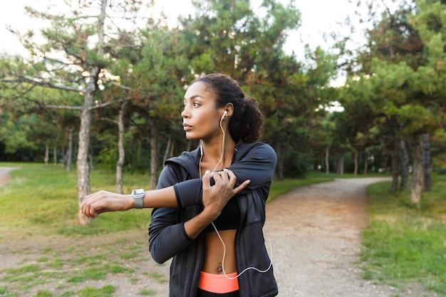 Portret van energieke afro-amerikaanse vrouw 20s dragen zwarte trainingspak doen oefeningen, en haar lichaam uitrekken in groen park