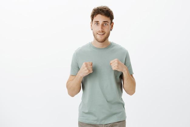 Portret van energieke charmante europese mannelijke collega in trendy t-shirt, gebalde vuisten opheffen en breed glimlachen, klaar om punch te geven of willen vechten