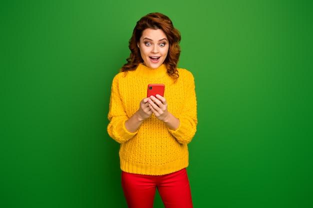 Portret van energieke gek verbaasd positieve vrolijke vrouw gebruik smartphone onder de indruk abonnees volgers schreeuw wow omg draag stijlvolle trendy pullover geïsoleerd heldere glans kleur muur