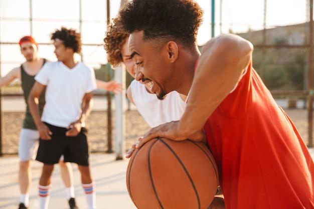 Portret van energieke sportieve mannen spelen basketbal op de speelplaats buiten, tijdens zonnige zomerdag