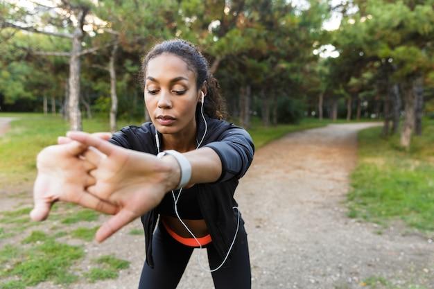 Portret van energieke sportvrouw 20s die zwarte trainingspak draagt die oefeningen doet, en haar lichaam in groen park uitrekt
