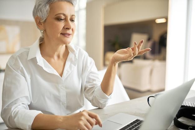 Portret van energieke succesvolle rijpe zakenvrouw in wit overhemd met online zakelijke bijeenkomst via videoconferentiegesprek, emotioneel gebaren, overeenkomst bespreken