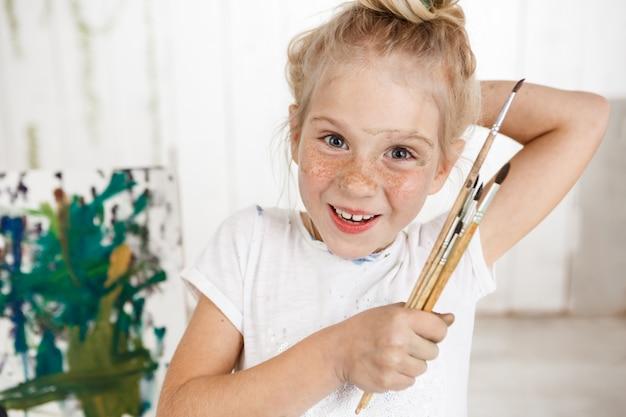Portret van engelachtige vrolijke lachend met tanden kind in witte ochtend licht in kunst kamer, met in haar hand bos van borstels. weinig europees meisje dat met blond haar het gelukkige en blije tonen kijkt