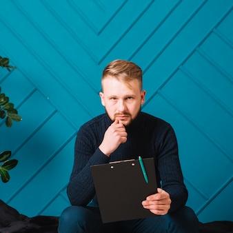 Portret van ernstig droevig de holdingsklembord van de blonde jonge mens met pen