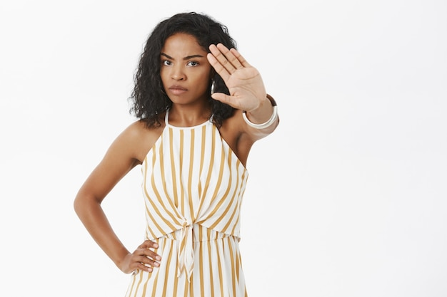 Portret van ernstig ogende intens en humeurig gehinderd afro-amerikaanse vrouw die hand naar camera trekt om gezicht te bedekken