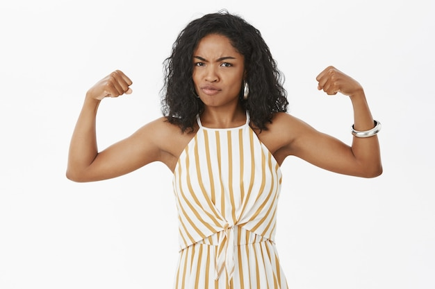 Portret van ernstig ogende sterke en krachtige afro-amerikaanse vrouw met krullend kapsel in elegante gestreepte overall