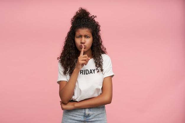 Portret van ernstig uitziende jonge krullende langharige brunette dame met donkere huid, fronsende wenkbrauwen en wijsvinger op haar lippen houden, vragen om stilte te houden, geïsoleerd op roze